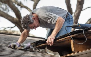Roofer examines a roof leak - roofing companies Essex MD - Claddagh Construction