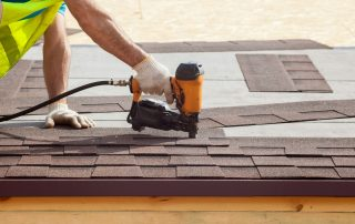 Man installing new roof shingles - roofing contractor in essex md - Claddagh Construction
